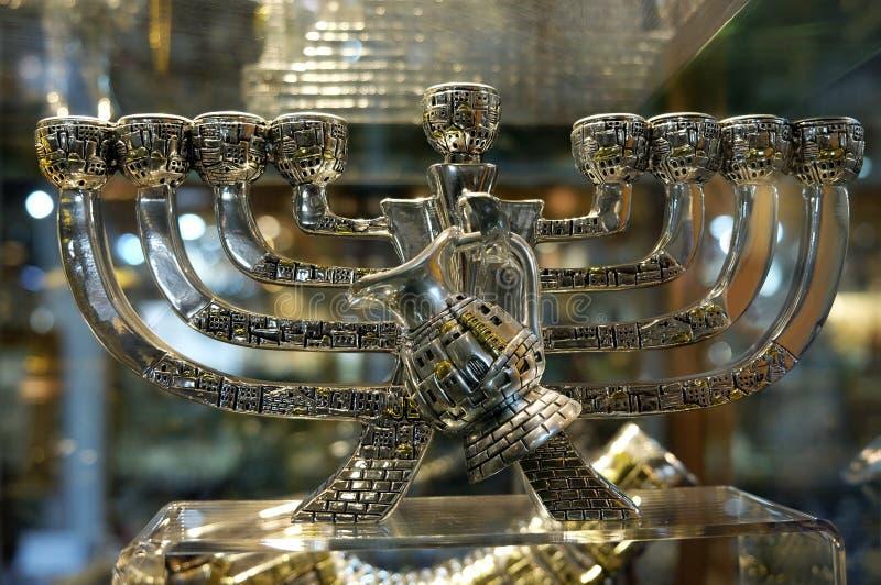 Chandelier de Hanoukka avec une cruche d'huile dans la fenêtre du souv photos stock