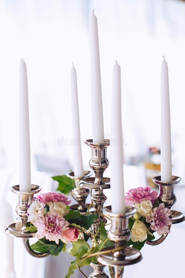 Chandelier en métal de mariage avec des bougies décorées des fleurs image stock