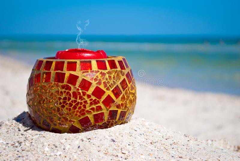 Chandelier en verre et une bougie rouge sur le sable sur un fond de mer bleue et de ciel bleu photos stock