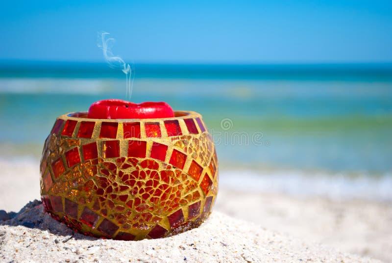 Chandelier en verre et une bougie rouge sur le sable sur un fond de mer bleue et de ciel bleu image libre de droits