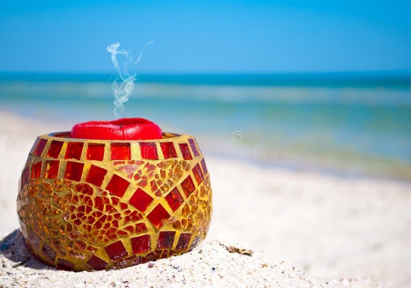Chandelier en verre et une bougie rouge sur le sable sur un fond de mer bleue et de ciel bleu photo stock