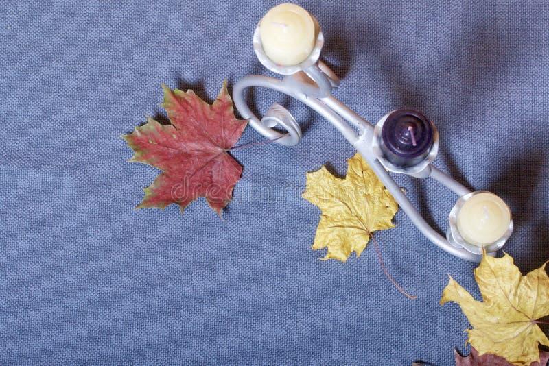 Chandelier forgé en métal avec des bougies Des feuilles d'automne tombées de jaune et de rouge sont dispersées sur la surface photo stock