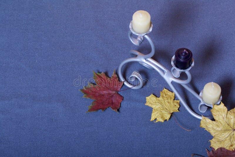 Chandelier forgé en métal avec des bougies Des feuilles d'automne tombées de jaune et de rouge sont dispersées sur la surface photographie stock