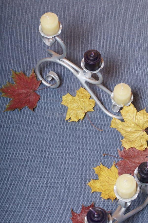 Chandelier forgé en métal avec des bougies Des feuilles d'automne tombées de jaune et de rouge sont dispersées sur la surface images stock