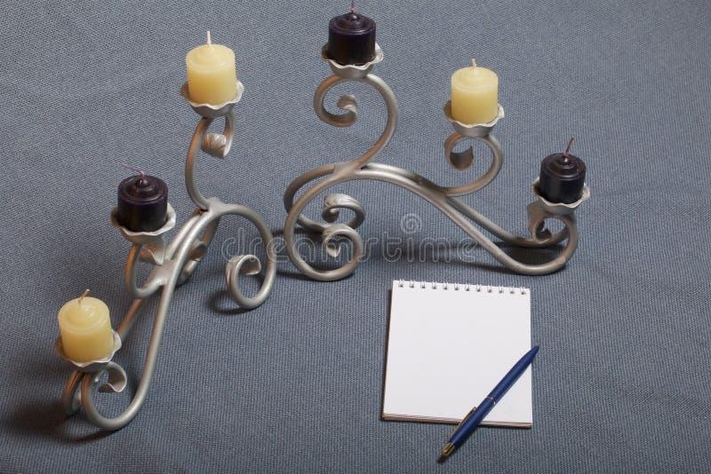 Chandelier forgé en métal avec des bougies Il y a un bloc-notes ouvert et un stylo photographie stock