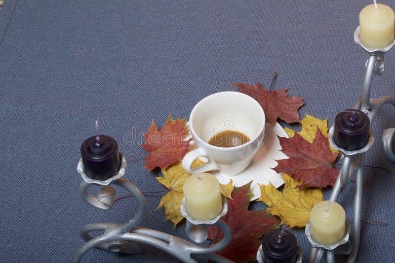 Chandelier forgé en métal avec des bougies Une tasse avec du café inapprouvé Des feuilles d'automne tombées de jaune et de rouge  images stock
