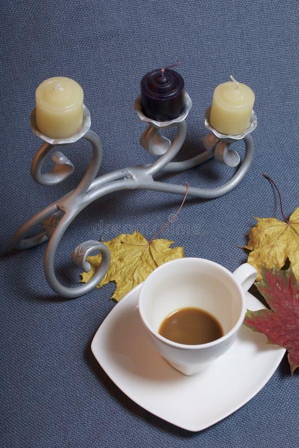 Chandelier forgé en métal avec des bougies Une tasse avec du café inapprouvé Des feuilles d'automne tombées de jaune et de rouge  photographie stock libre de droits