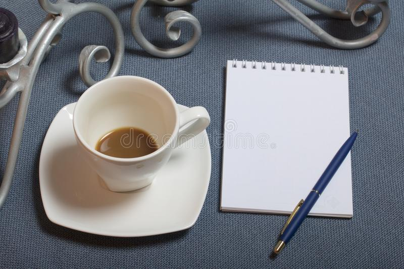 Chandelier forgé en métal avec des bougies Une tasse avec du café inapprouvé Il y a un bloc-notes ouvert et un stylo Feuilles d'a images libres de droits