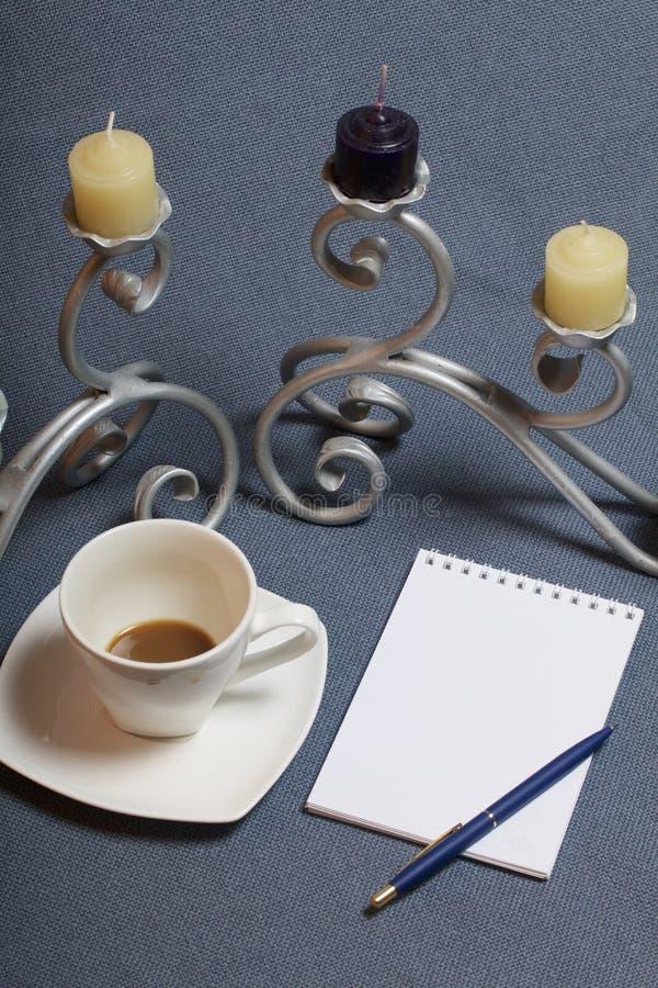 Chandelier forgé en métal avec des bougies Une tasse avec du café inapprouvé Il y a un bloc-notes ouvert et un stylo Feuilles d'a photo stock