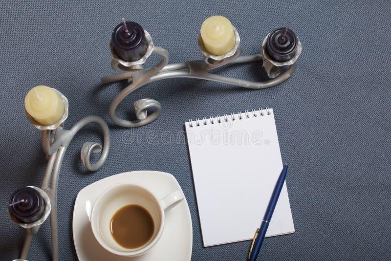 Chandelier forgé en métal avec des bougies Une tasse avec du café inapprouvé Il y a un bloc-notes ouvert et un stylo Feuilles d'a image stock
