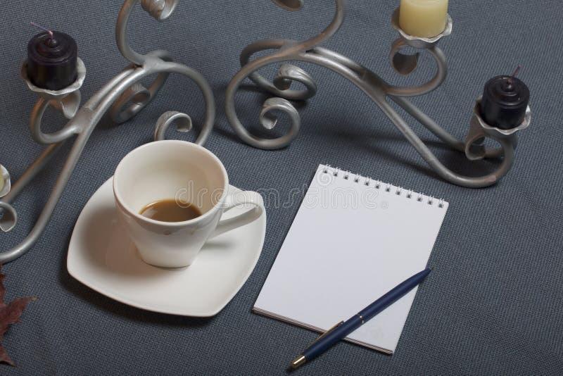 Chandelier forgé en métal avec des bougies Une tasse avec du café inapprouvé Il y a un bloc-notes ouvert et un stylo Feuilles d'a photos libres de droits