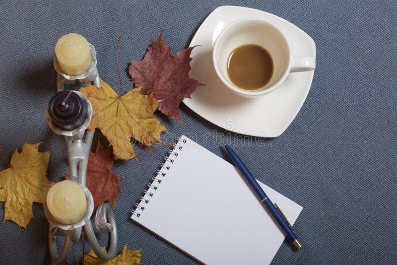 Chandelier forgé en métal avec des bougies Une tasse avec du café inapprouvé Il y a un bloc-notes ouvert et un stylo Feuilles d'a images stock