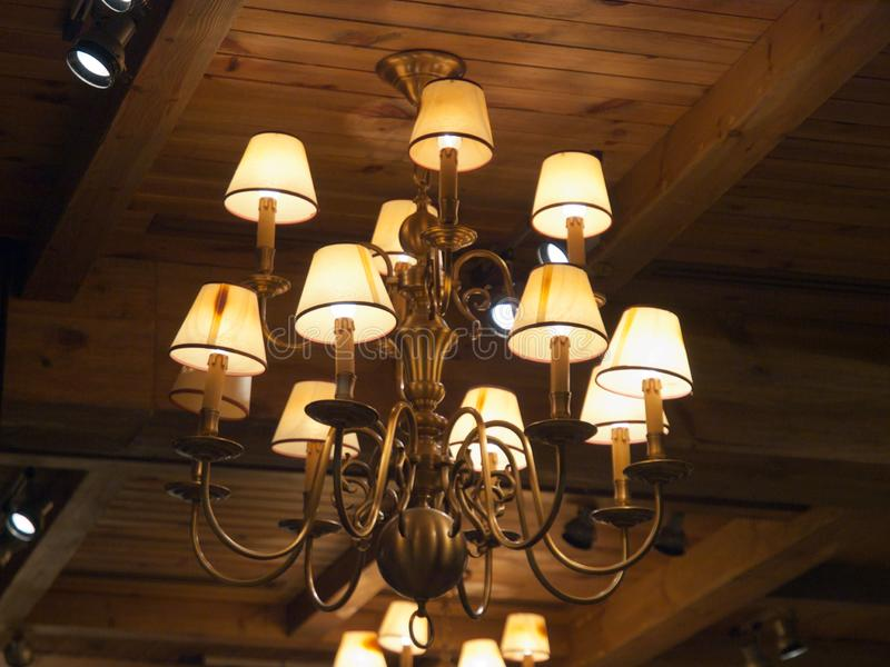 Romantic diner under an old rustic chandelier. Rustic, old chandelier that light this modern day living stock photography