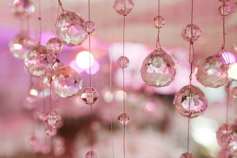 Chandelier light in interior, Chrystals close-up. crystal part from chandelier. Pink colors.  stock photos
