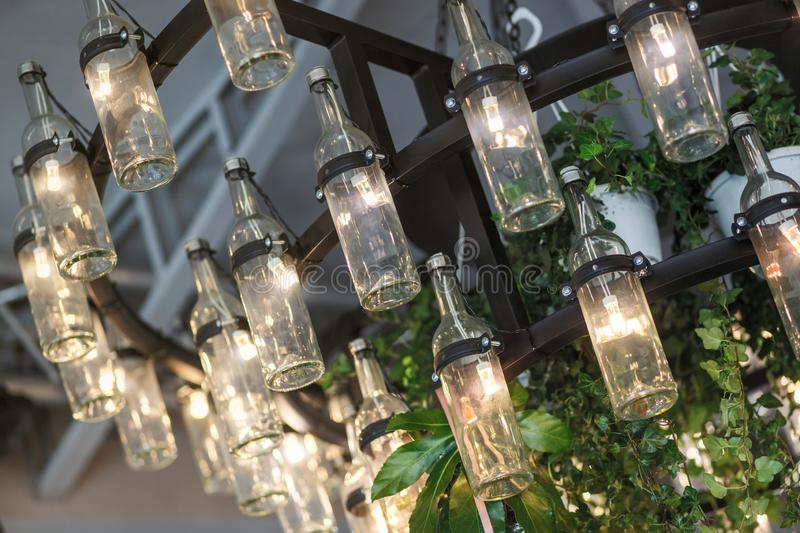 Chandelier with luminous bottle-shaped bulbs and plants stock photo