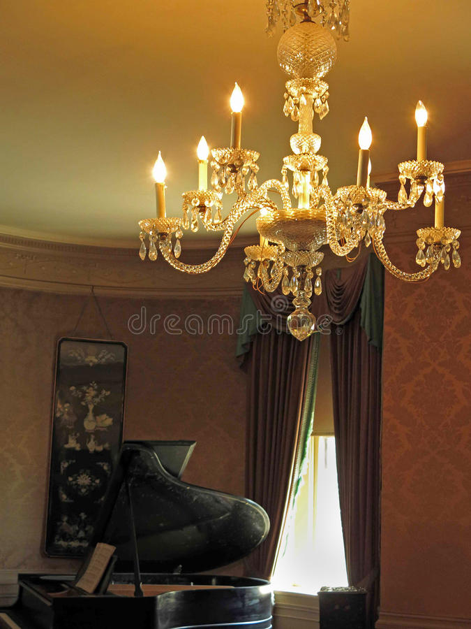 Grand piano and lighted chandelier. Grand piano and lighted gold chandelier with six lights stock photography