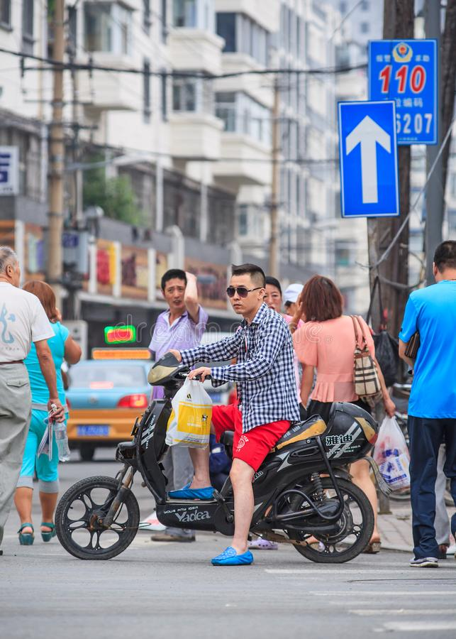 Fashionable young man on a black electric scooter, Changchun, China royalty free stock photos