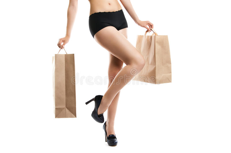 Change clothes. update the style. concept. The woman holds in hands of buying. Shapely female legs close-up on a white background. Woman in high heels shoes stock image