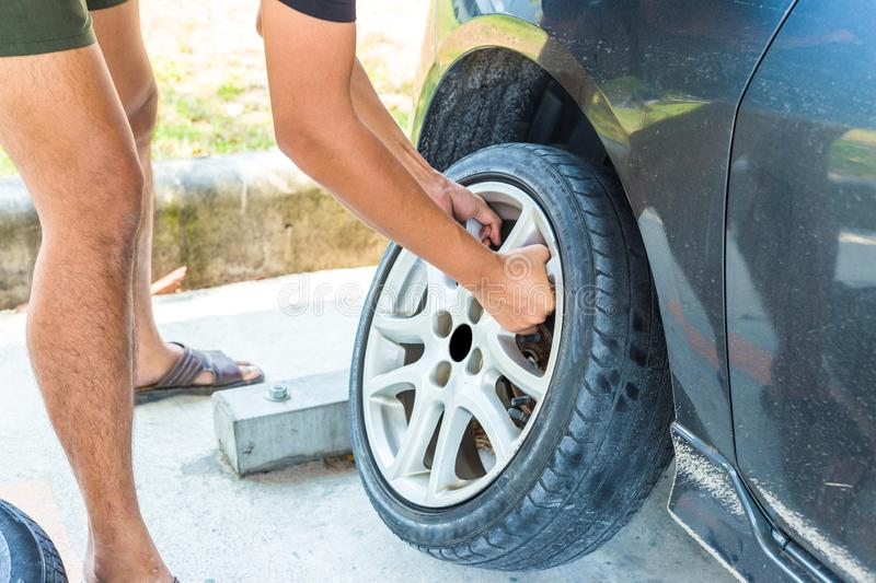 Change a flat car tire at car park with Tire maintenance, damaged car tyre stock photography