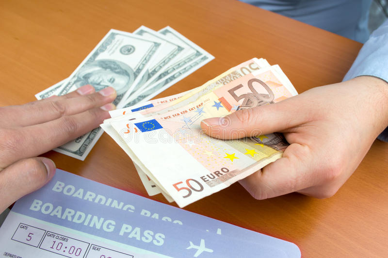 Change money at the airport. Close up a money changing hands of people in an airport stock photo