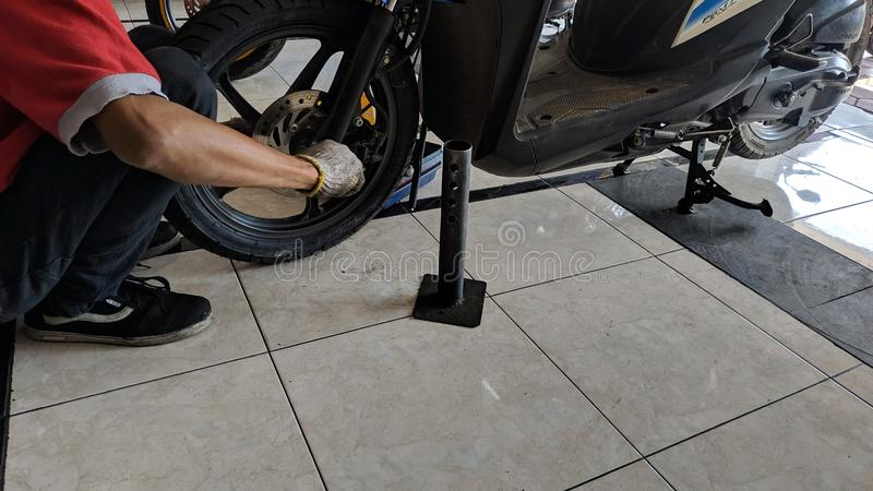 Change motorcycle tires in the machine shop. Bike shop stock images
