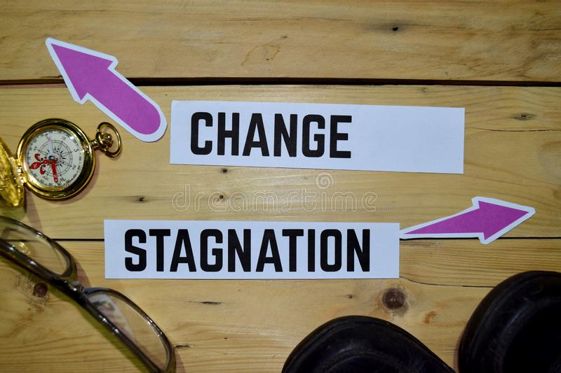 Change or Stagnation opposite direction signs with boots, eyeglasse and compass on wooden. Vintage background. Business and education on inspiration concepts stock image