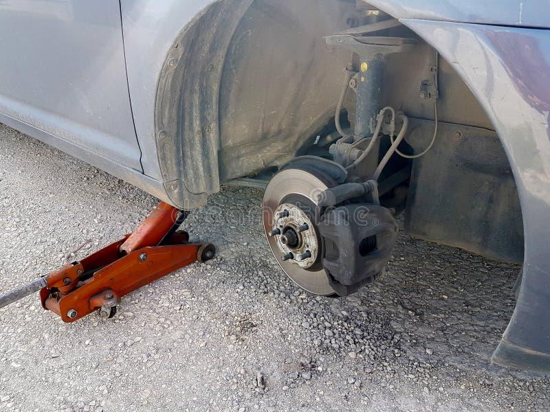 Changement de pneu crevé de voiture remplacer sur l'urgence de problème de route photos libres de droits