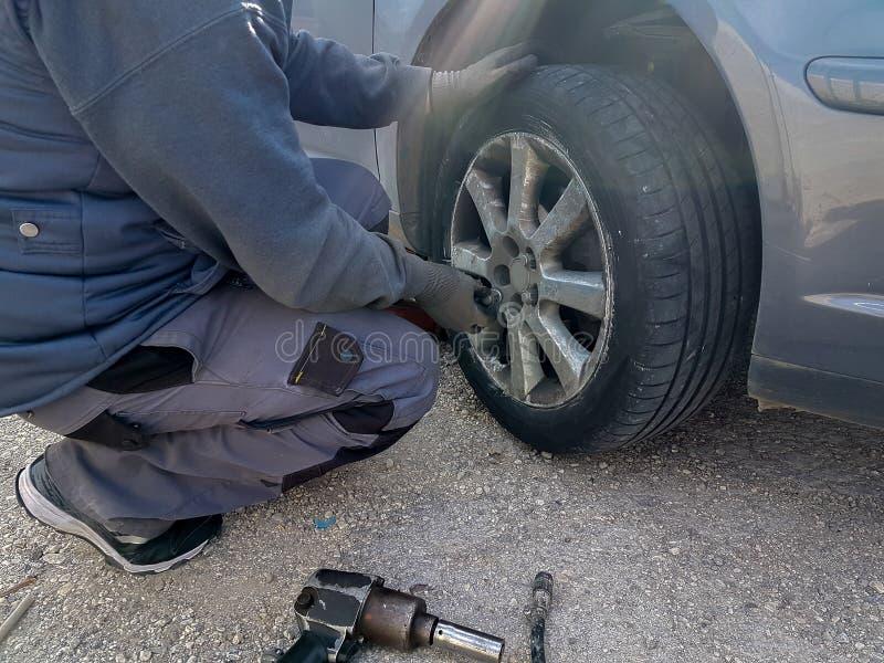Changement de pneu crevé de voiture remplacer sur l'urgence de problème de route images libres de droits