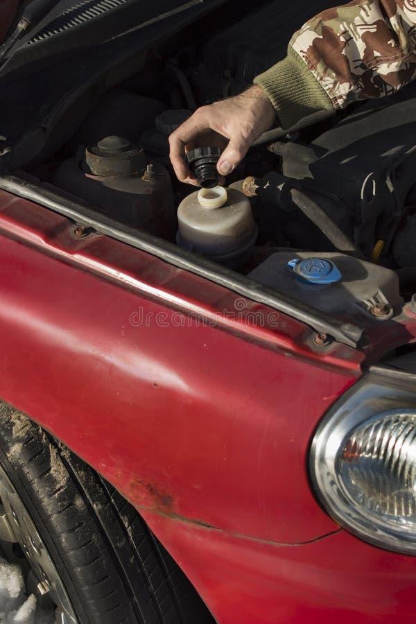 Changement liquide de direction Le mécanicien remplit fluide de direction assistée de réservoir photos libres de droits