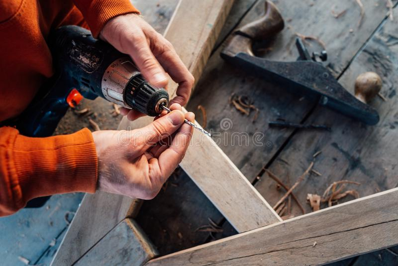 Changements de travailleur une perceuse dedans un tournevis, dans la perspective d'une table en bois photographie stock libre de droits