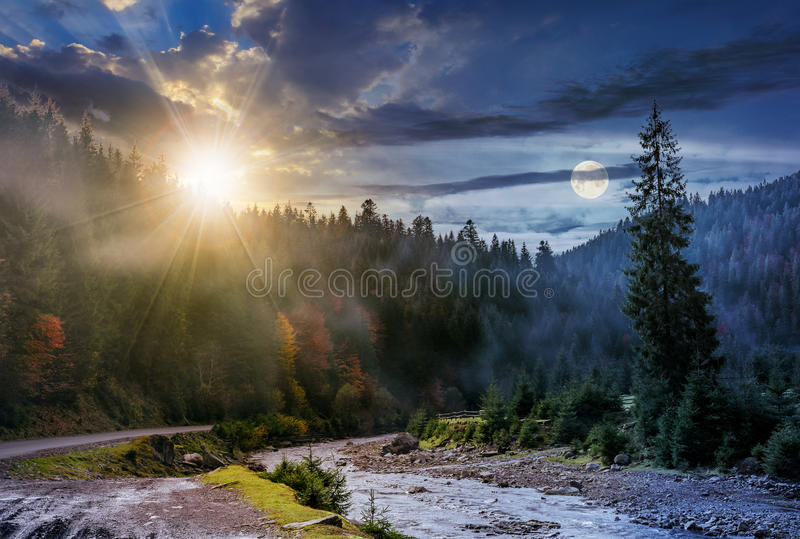 Changez jour et nuit au-dessus de la forêt et de la rivière brumeuses photos libres de droits