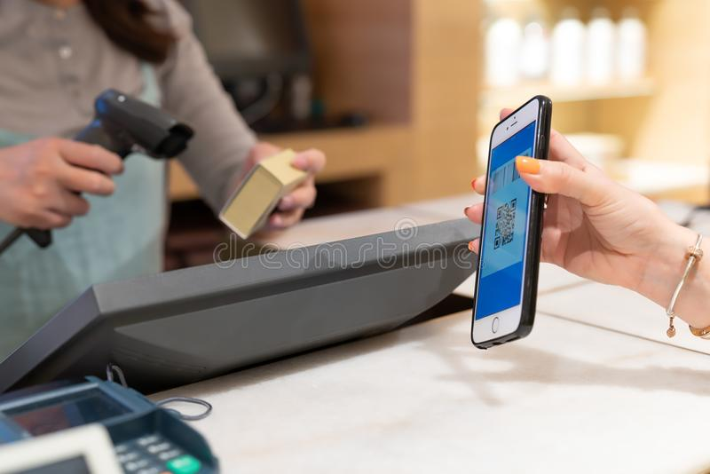 CHANGHAÏ, CHINE - MAI 2018 : Paiement de code de Qr, achats en ligne, prise de main de femmes le smartphone pour le paiement photographie stock libre de droits