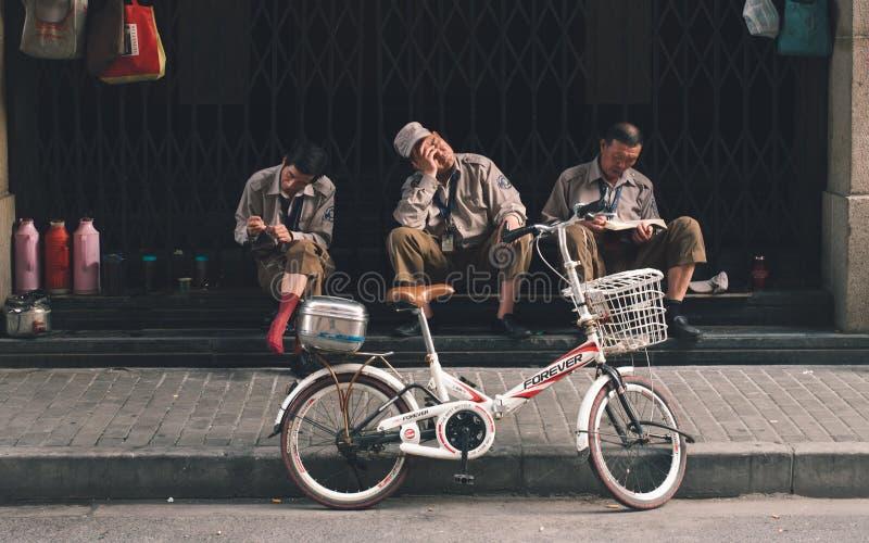 CHANGHAÏ, CHINE : Trois travailleurs cassent le temps, se reposant photographie stock libre de droits