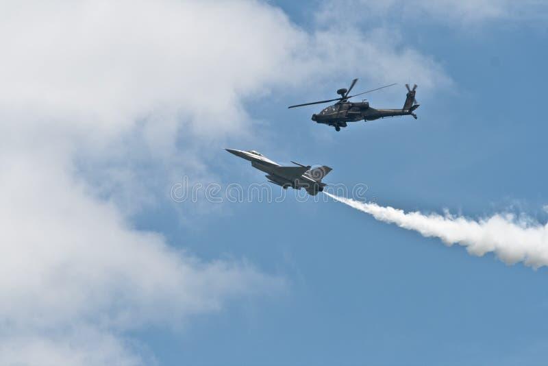 Changi, Singapura - fevereiro 6,2010: Helicóptero de ataque de RSAF AH-64 Apache e uma luta de RSAF F-16C imagens de stock