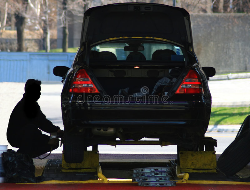 Changing Car Tires. A mechanic installs new tires on a car royalty free stock photography
