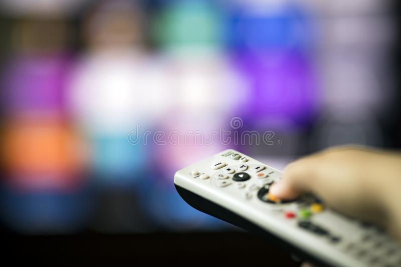 Remote control in hand in front of smart tv. Changing chanels with remote control in front of smart tv stock photos