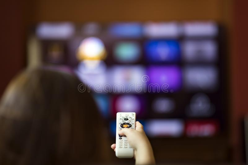 Remote control in hand in front of smart tv. Changing chanels with remote control in front of smart tv stock images