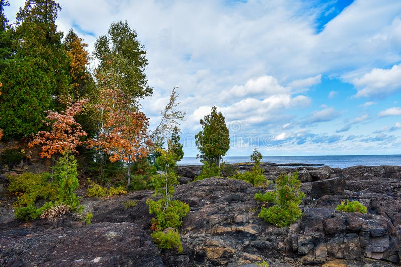 Autumn Day bright blue skies peaking through the clouds overlooking Lake Superior. Changing Colors on Presque Isle, Marquette, Michigan. Volcanic rocks royalty free stock photo
