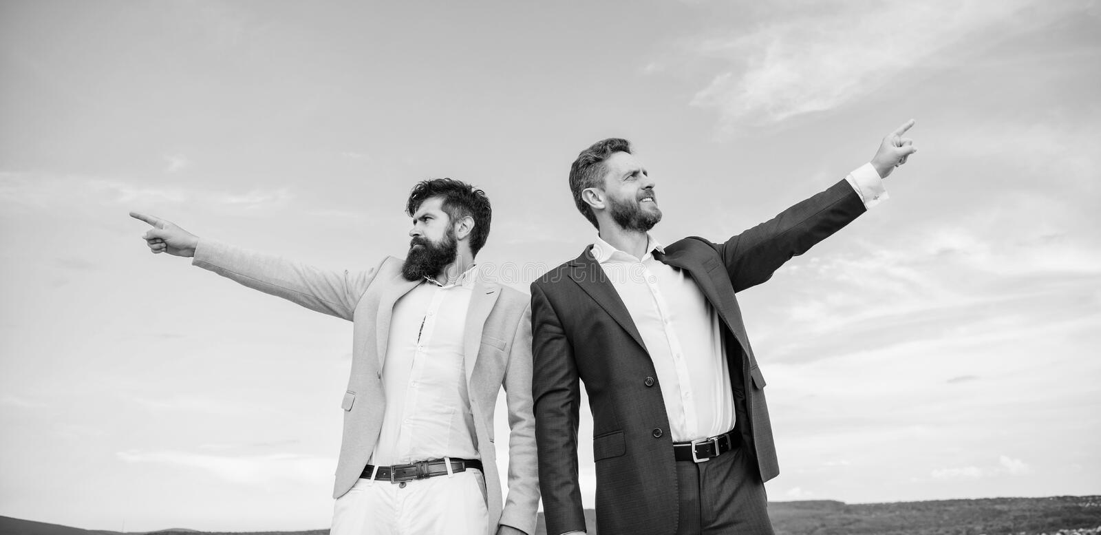 Changing course. Men formal suit managers pointing at opposite directions. New business directions. Developing business stock image