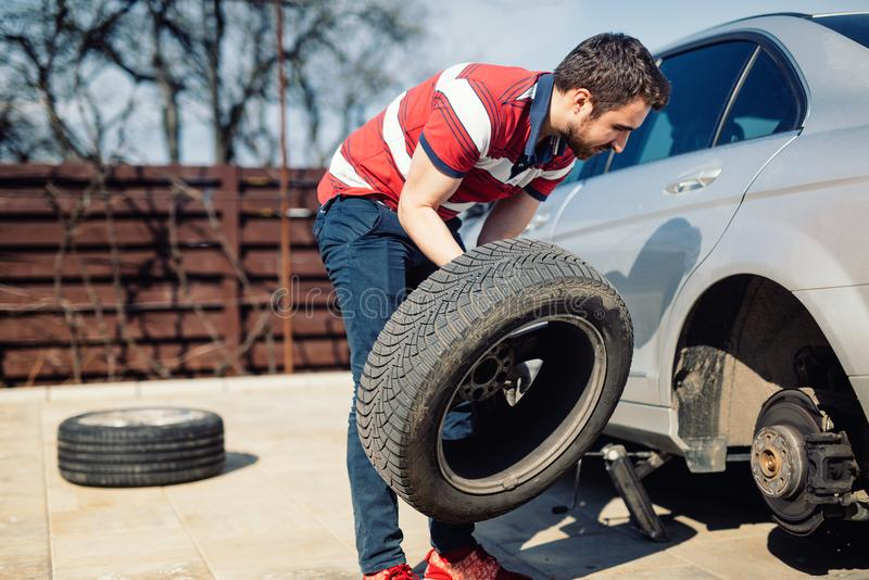 Changing a flat car tire in the backyard. Tire maintenance, damaged car tyre or changing seasonal tires. Changing a flat car tire. Tire maintenance, damaged car royalty free stock image