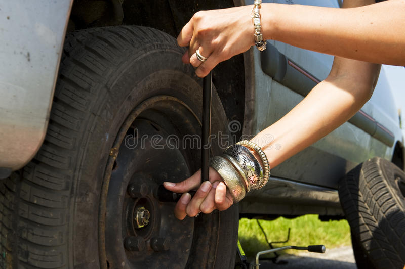Changing a flat tire. Woman, loosening the bolts on a wheel to change a flat tire royalty free stock photo