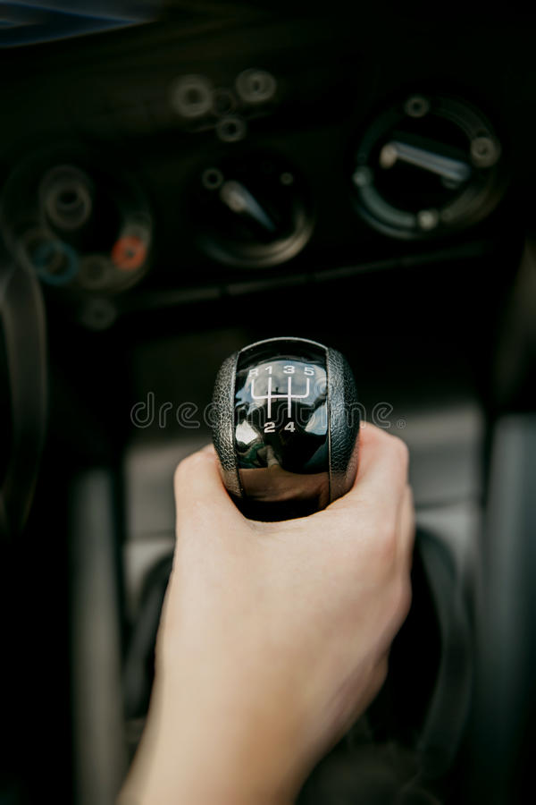 Changing manual car shift gear. Manual car shift gear changed by hand in automobile interior stock images