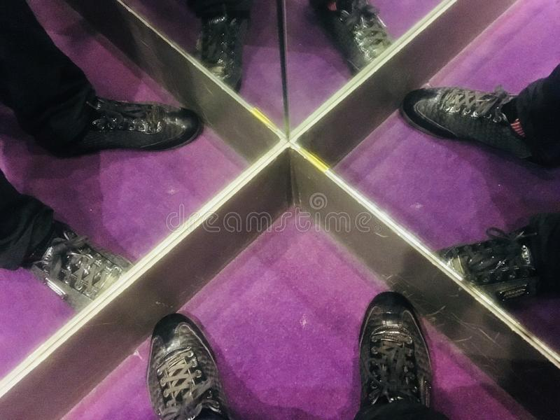 Changing Room. Standing in the corner of the changing room at Impeccable Formal Wear, Hatch End, Greater London. Purple carpet. Mirrored sides. Winter shopping royalty free stock image