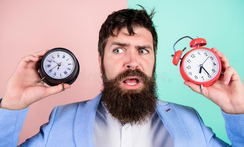 Changing time zones affect health. Time zone. Does changing clock mess with your health. Man bearded hipster hold two stock photos