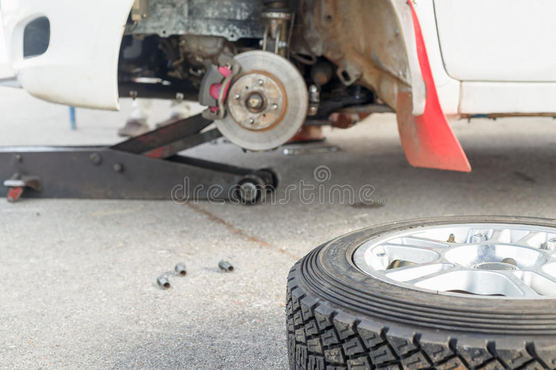 Changing a tire on a rally car in maintenance area. Changing a tire and breake pad on a rally car in maintenance area stock image