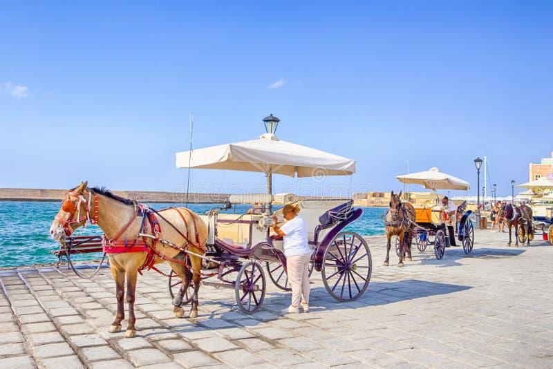 Chania, Крит - 20-ое августа 2018: Одна из достопримечательностей Chania с кабинами верховой езды и классики в Chania стоковая фотография