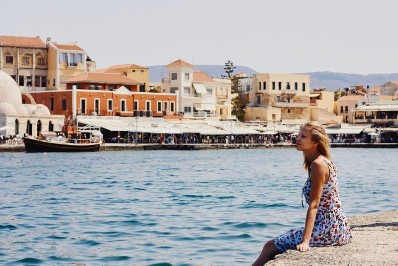 Chania, Creta, Grecia, il 10 settembre 2017: La ragazza sta sedendosi sull'argine nel vecchio porto veneziano e sta esaminando la immagine stock