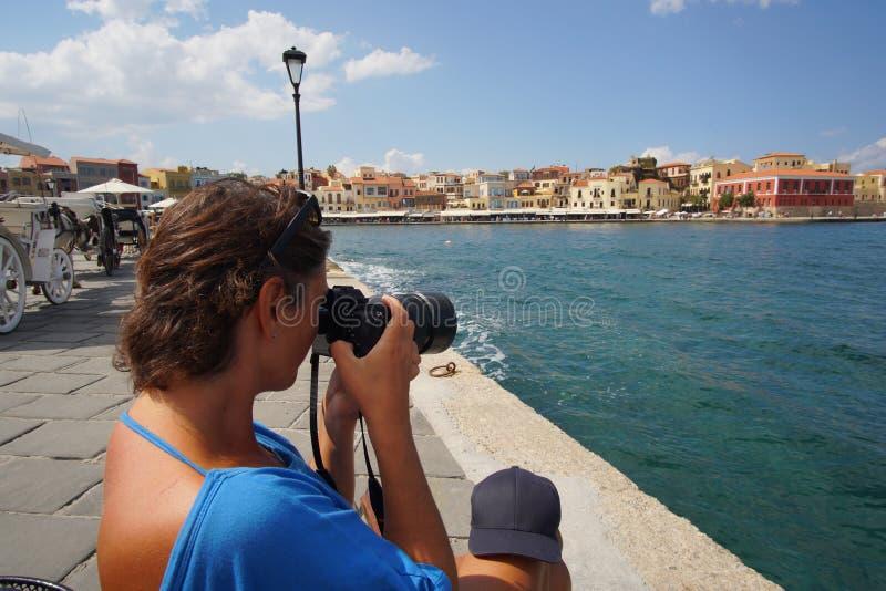 Chania, Creta, o 1º de outubro de 2018 um turista toma uma imagem no porto Venetian velho imagens de stock royalty free
