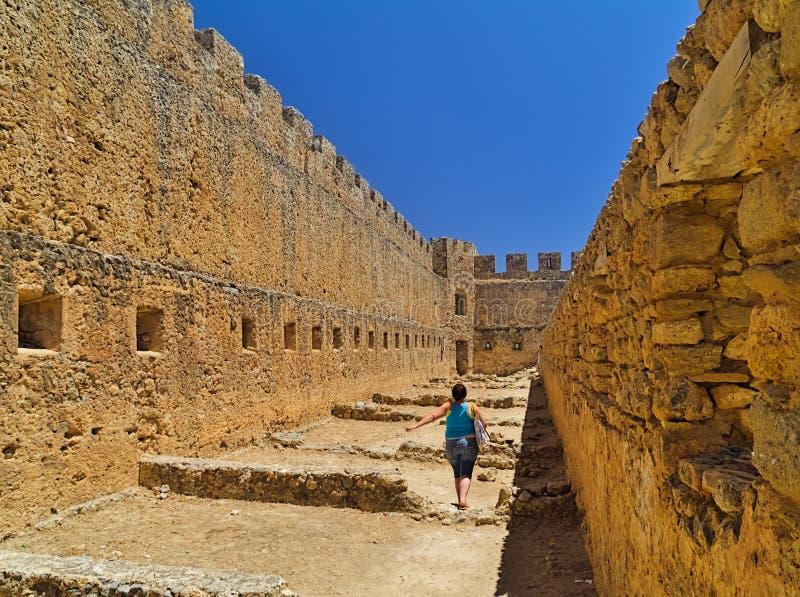 Woman walking inside Fragokastelo castle, bright summer day royalty free stock photography