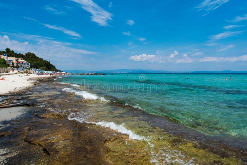 Chaniotis, Ελλάδα - 23 Ιουνίου 2018: Παραλία πόλεων Chaniotis Popullar σε Kassandra, Χαλκιδική με πολλούς τουρίστες που απολαμβάν στοκ φωτογραφία